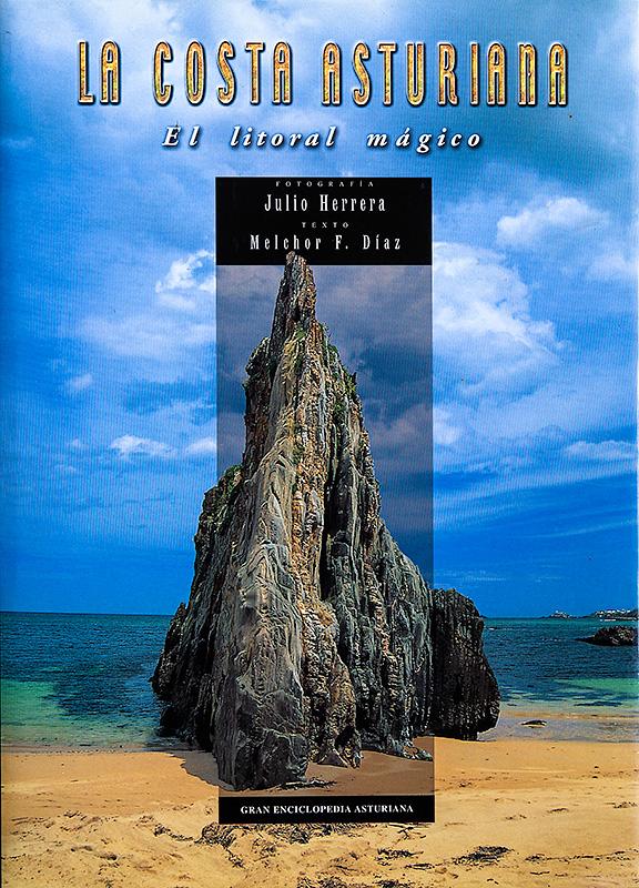 """Portada del libro de fotografías """"La costa asturiana, el litoral mágico"""" con la fotografía de la playa de Mexota con una cielo azul, un agua color verde esmeralda y una roca que emerge del agua en forma picuda y una arena muy limpia"""