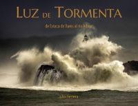 """Portada del libro de fotografías """"luz de tormenta. De Estaca de Bares al río Adour"""". La portada es el faro de la Isla de Mouro en Santander en el mar Cantábrico con una gran ola que lo envuelve."""