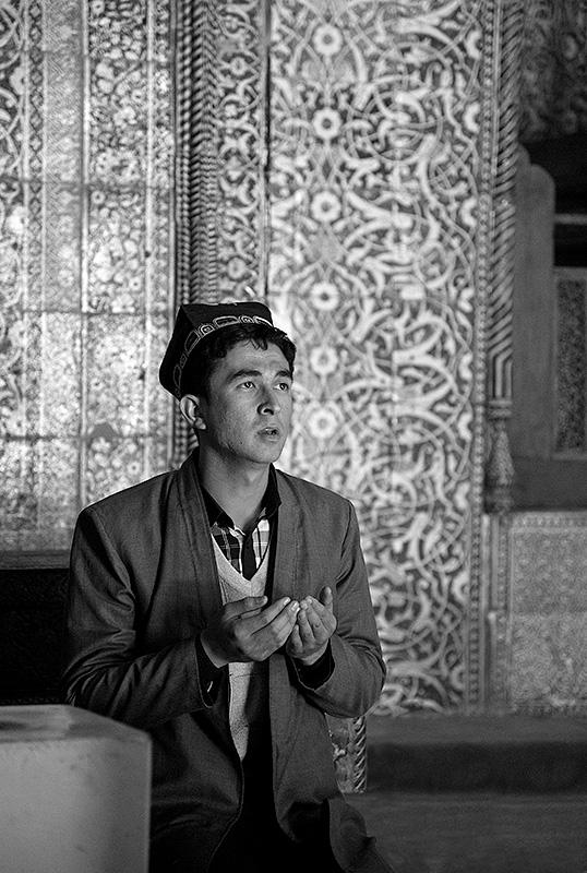 Hombre joven orando en Bukhara. Uzbekistán.